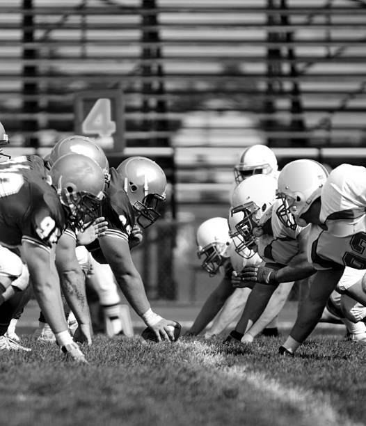 NCAA Football Line Black and white image of offensive and defensive linemen going head to head. football lineman stock pictures, royalty-free photos & images