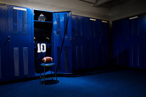 Football Locker Room An open locker with a jersey, helmet and ball in a authentic football locker room high school sports stock pictures, royalty-free photos & images