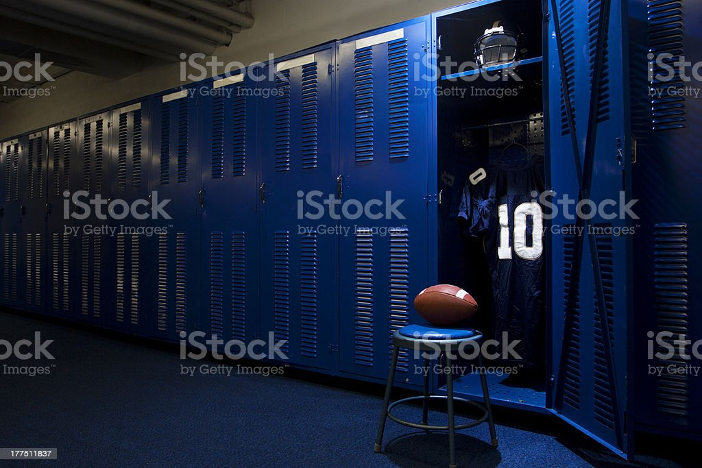 An open locker with a jersey, helmet and ball in a authentic football...