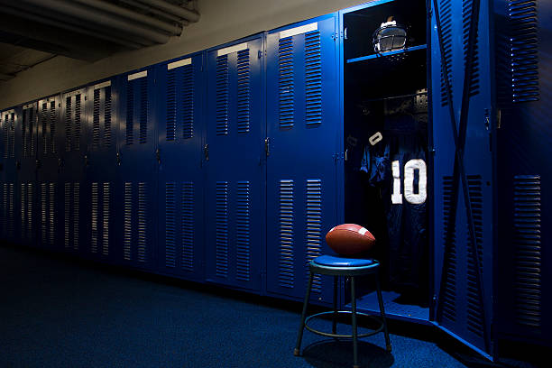 Football locker room with open locker An open locker with a jersey, helmet and ball in a authentic football locker room american football uniform stock pictures, royalty-free photos & images