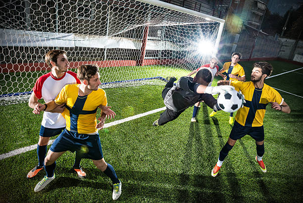 Football match in stadium: Goalkeeper save stock photo