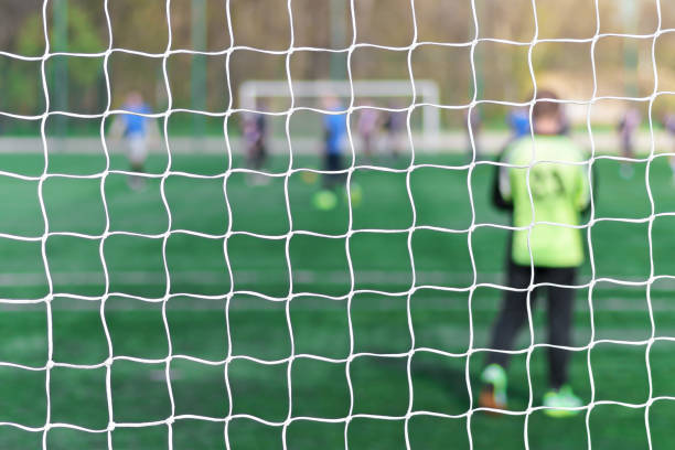 football net background over soccer field stadium - sports championship stock photos and pictures