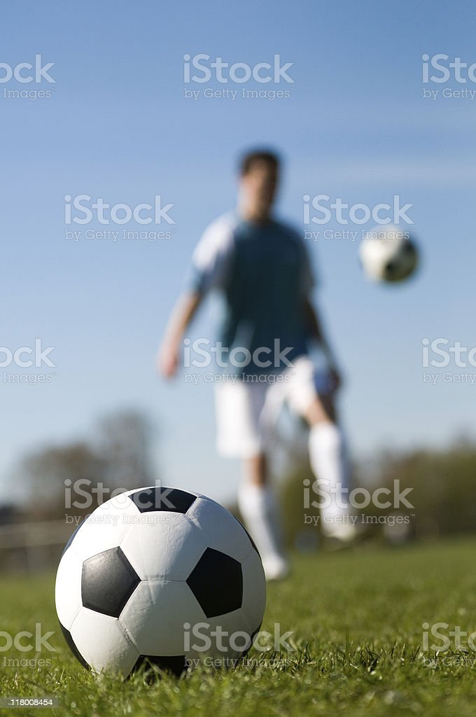 Football on a soccer field and player kicking ball royalty-free stock photo