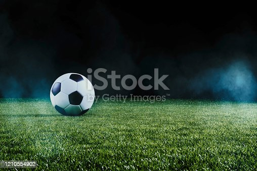 Football on an illuminated empty sports field at night backlit by bright spotlights in a low angle view with shadow, mist and copy space