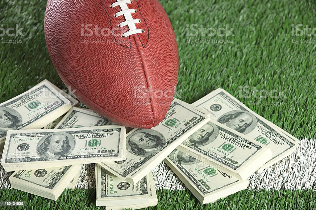 NFL football on field with a pile of money stock photo