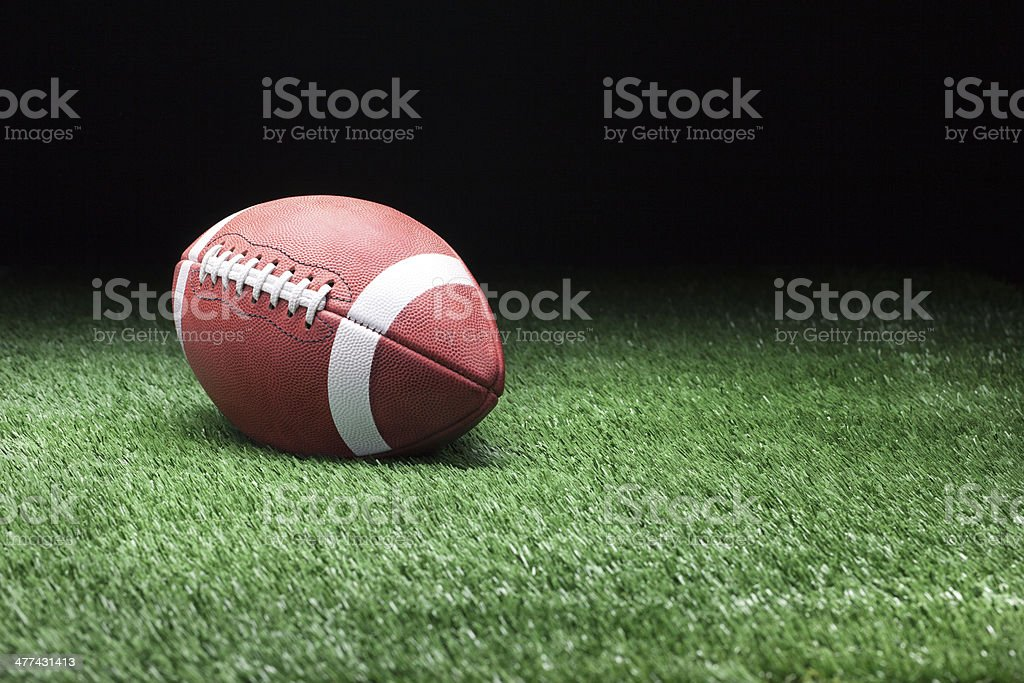 Football on grass against dark background stock photo