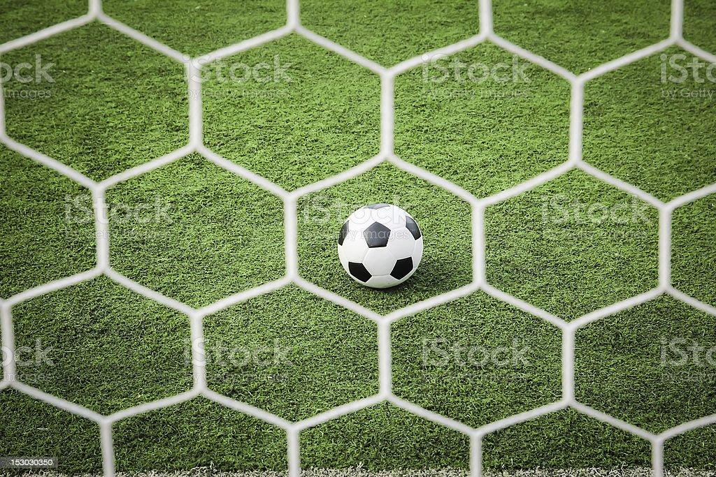 Pallone da calcio su erba verde davanti alla rete foto stock royalty-free