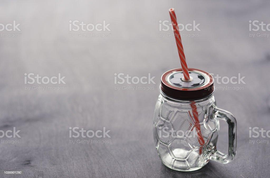 símbolo de bola de futebol ou futebol em uma tampa de vidro de cerveja, com uma palha listrada - foto de acervo