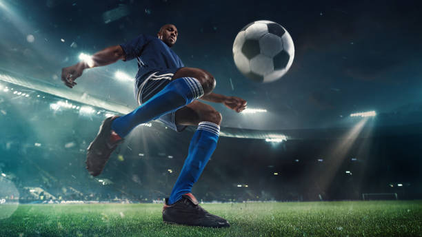 Football or soccer player in action on stadium with flashlights, kicking ball for winning goal, wide angle. Action, competition in motion stock photo