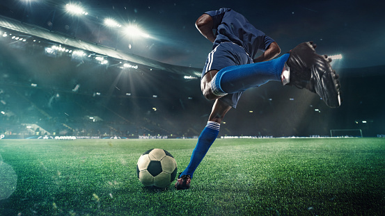 Football or soccer player in action on stadium with flashlights, kicking ball for winning goal, wide angle. Action, competition in motion