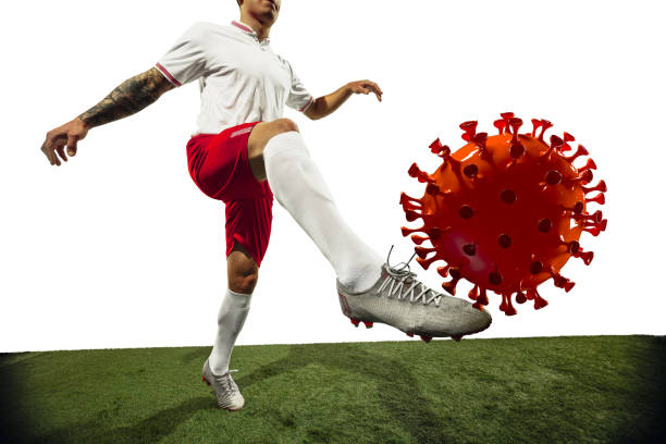Football or soccer player kicking, punching model of coronavirus - fighting with epidemic concept stock photo
