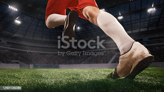 Excited running, aspirated. Football or soccer player on full stadium and flashlights background. Cropped close up with copyspace. Concept of sport, competition, winning, action and motion.