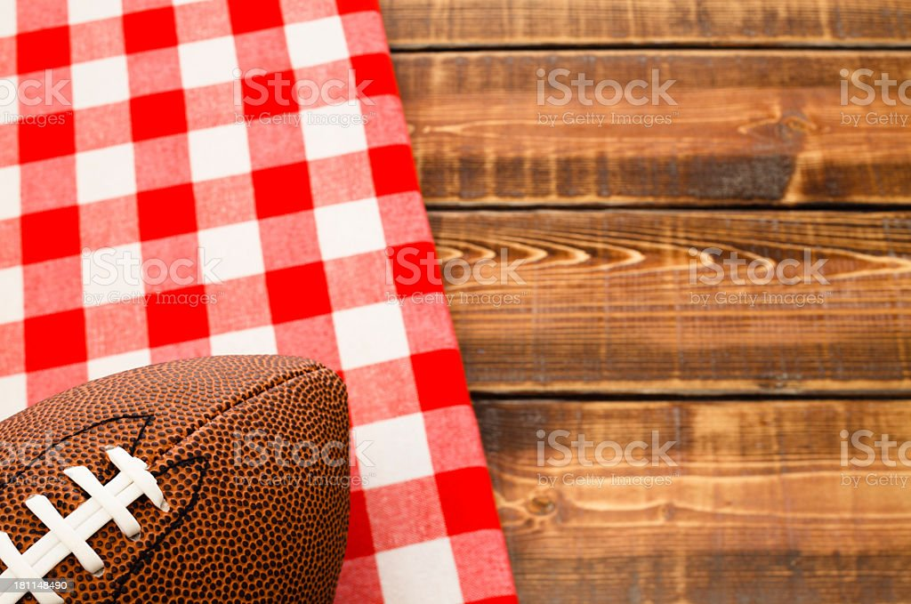 Football over a red and white cloth on a wooden table stock photo