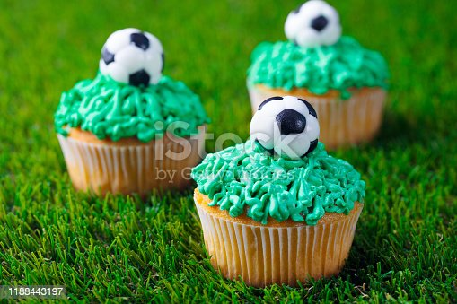 istock Football party, birthday decorated cupcake on green grass background. Close up. 1188443197