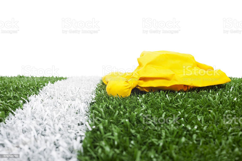 football penalty flag on grass by yard line royalty-free stock photo