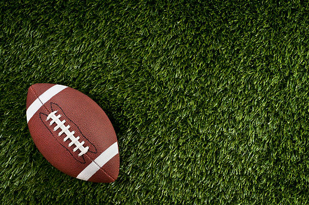 Football Football on blank football field.  Please see my portfolio for other sports related images. ncaa college football stock pictures, royalty-free photos & images