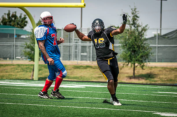 Football play in progress - XI Football players on the field playing the game. Celebrating touchdown. line of scrimmage stock pictures, royalty-free photos & images