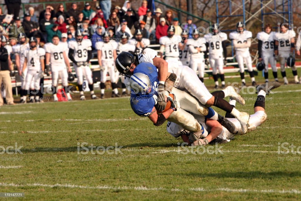 A football player being tackled in a game stock photo