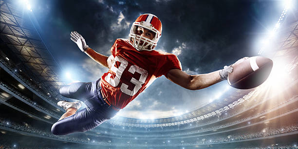 Football player catches a ball Professional football player catches a ball. The action takes place on professional stadium. The player wears unbranded sports uniform. There is artificial light on stadium together with sunlight. wide receiver athlete stock pictures, royalty-free photos & images