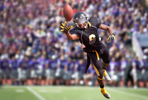 Football Player Diving to Catch a Football in Stadium.
