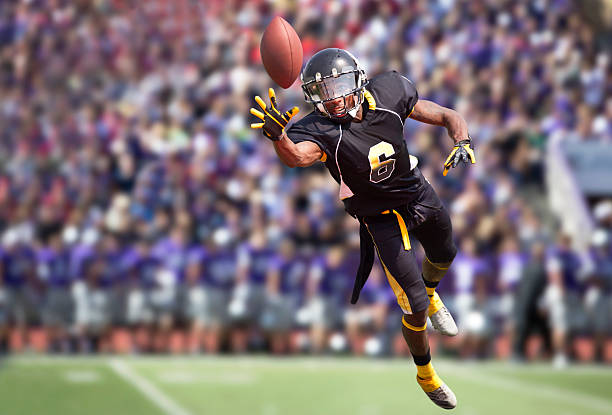 Football Player Diving to Catch a Football in Stadium. Wide receiver diving to make a catch with opposing team and fans in background. wide receiver athlete stock pictures, royalty-free photos & images