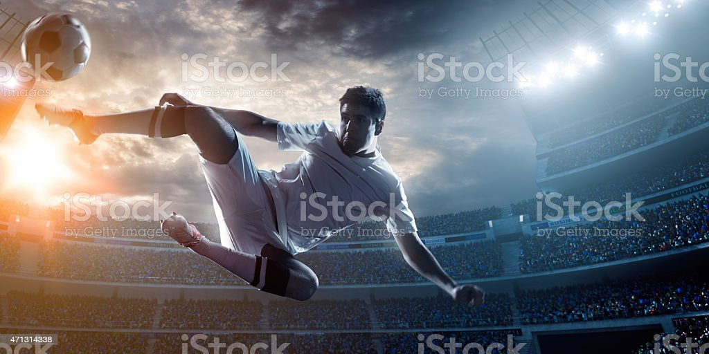 A football player doing a in air kick in a stadium stock photo