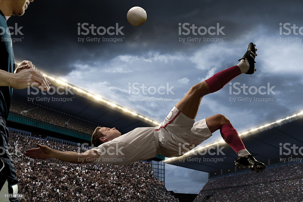 football player doing overhead kick stock photo