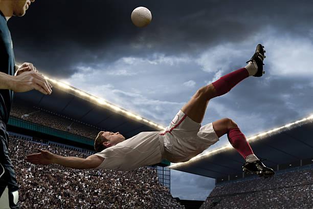 football player doing overhead kick stock photo