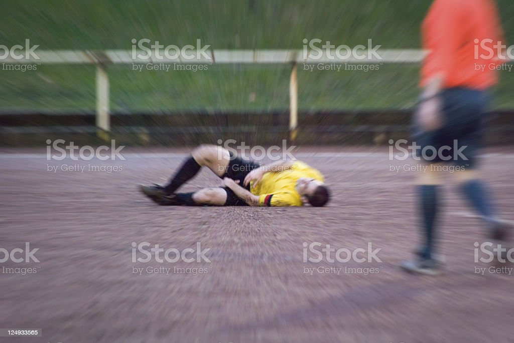 Football player fouled during soccer match, lying on field stock photo