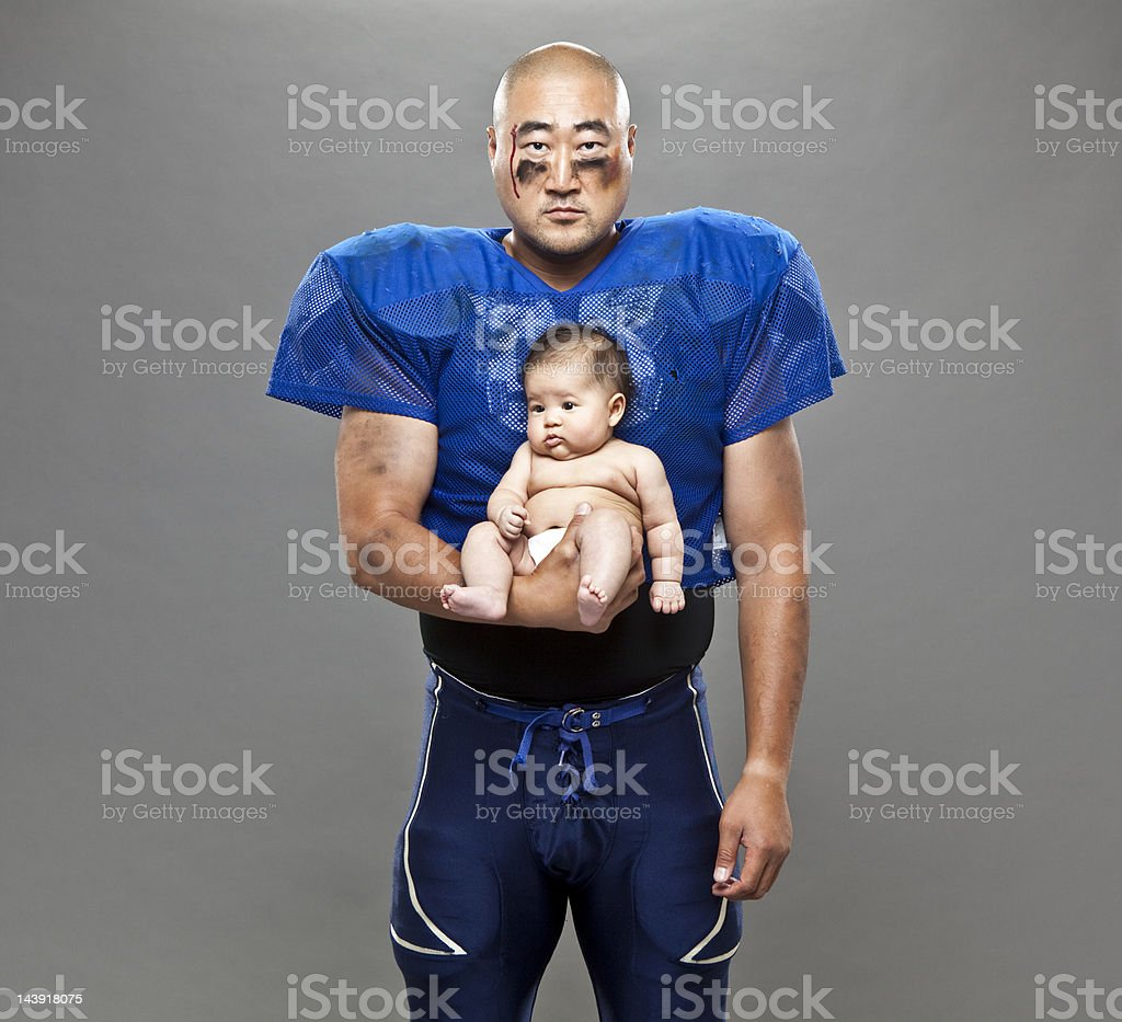 football player holding baby stock photo