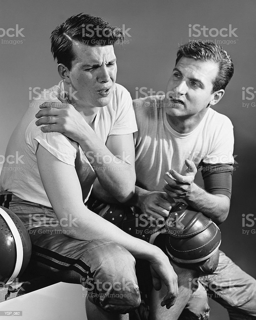 Football player holding sore shoulder; trainer sitting beside him royalty-free stock photo