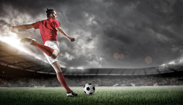 Football player in action on stadium background. stock photo
