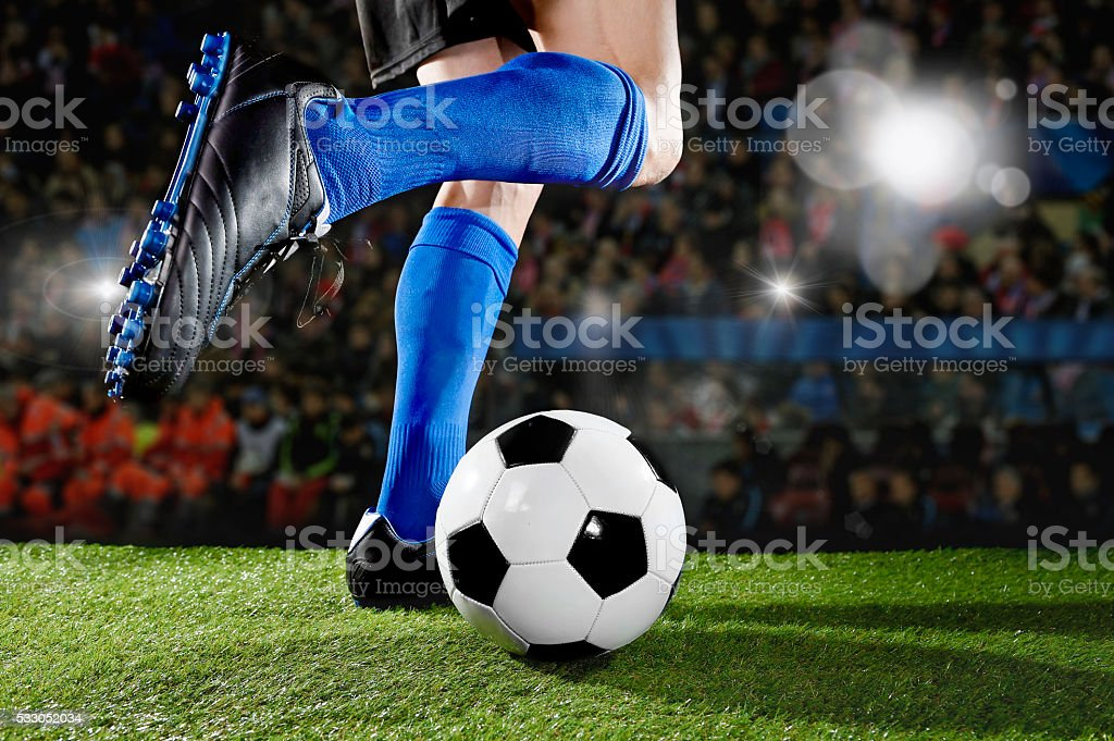 close up legs and feet of football player in action wearing blue...