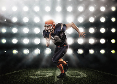 Football player in blue uniform on grass illuminated by floodlights