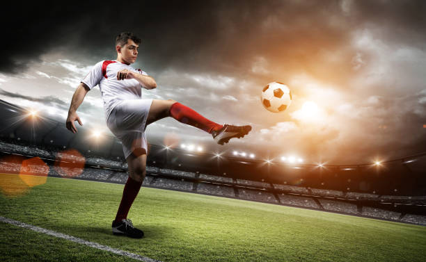 football player is kicking a ball in the stadium. - sports championship stock photos and pictures