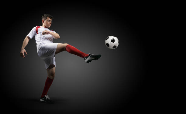 football player is kicking a ball on the black background. - sports championship stock photos and pictures