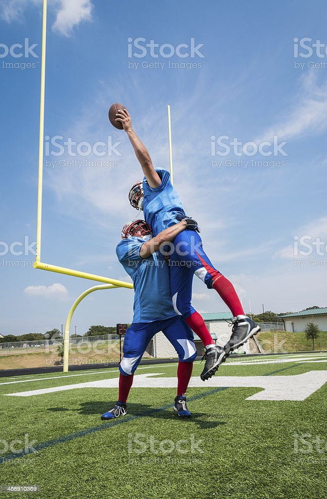 Football Player Jumping to Catch Ball for Touchdown in Endzone stock photo