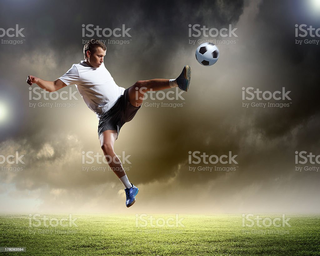 Football player jumping to kick ball in midair royalty-free stock photo