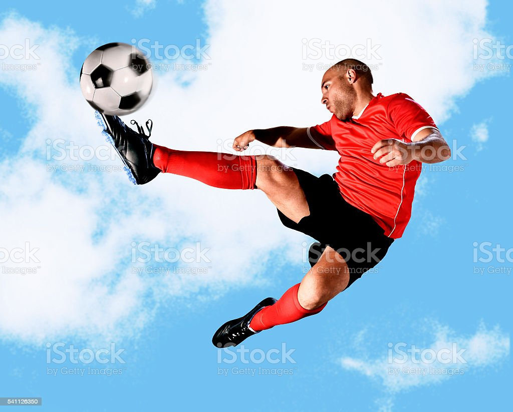 young football player kick ball in skillful volley jumping on the air...