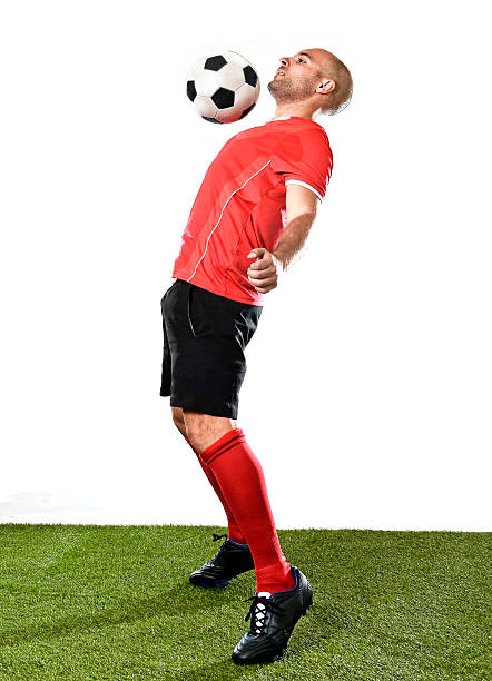 football player kicking controling ball with chest isolated background - fußball poster stock-fotos und bilder