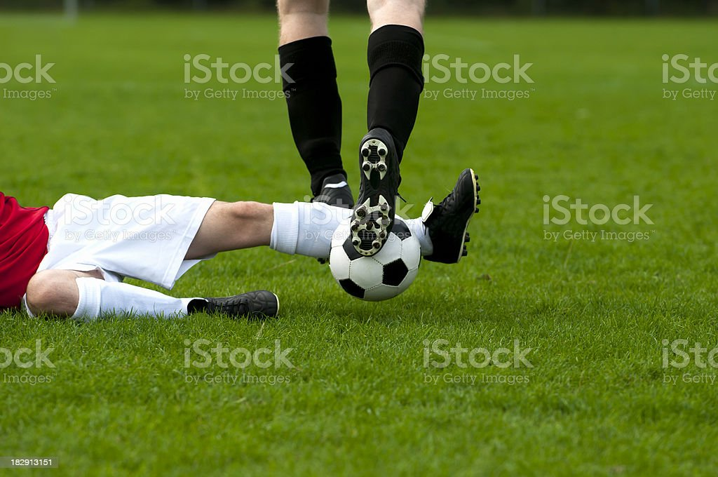 Football player makes tackling to get the soccer ball stock photo