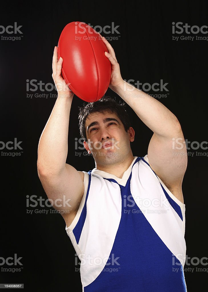 AFL Football Player Marks the ball royalty-free stock photo