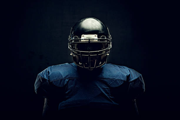 Football Player Intense portrait of a football athlete ready for game time. american football uniform stock pictures, royalty-free photos & images