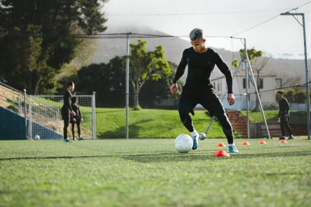 Prática de jogador de futebol drible no campo - foto de acervo