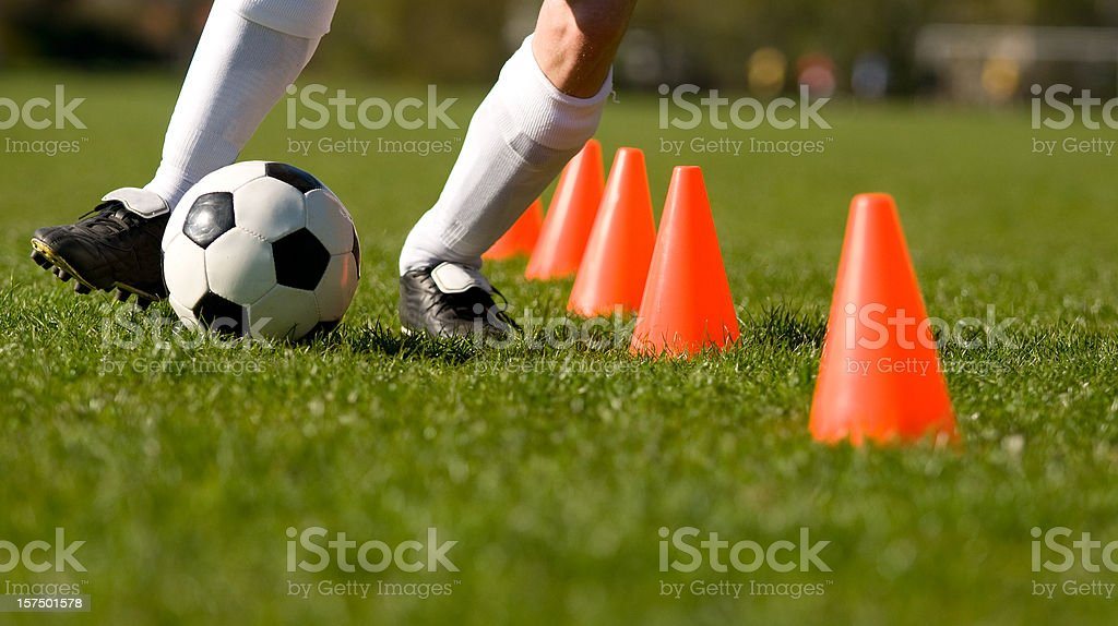 Football player pratices with a soccer ball stock photo