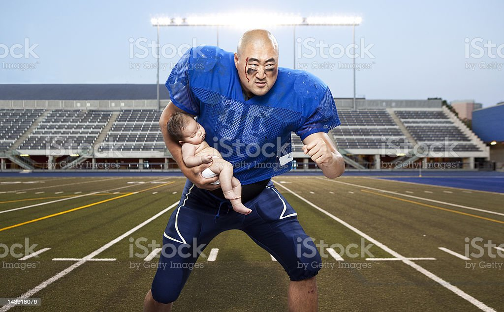 football player protecting baby stock photo