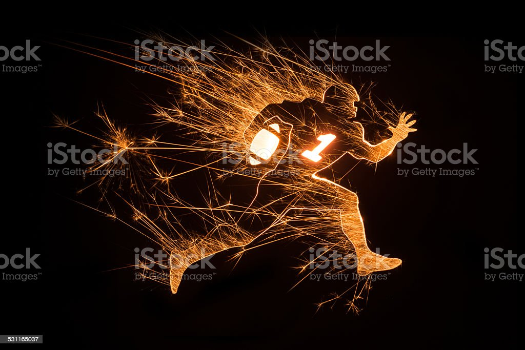 Football player running with ball on black background stock photo