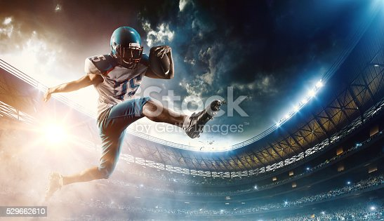 Professional football player (Running Back) runs with the ball. The action takes place on professional stadium. The player wears unbranded sports uniform. There is artificial light on stadium together with sunlight.
