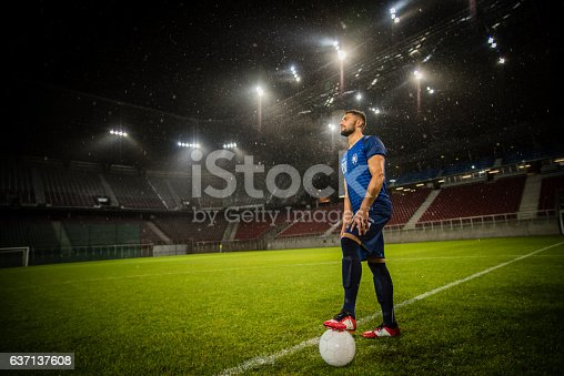 Young male football player standing with football on football pitch in stadium.