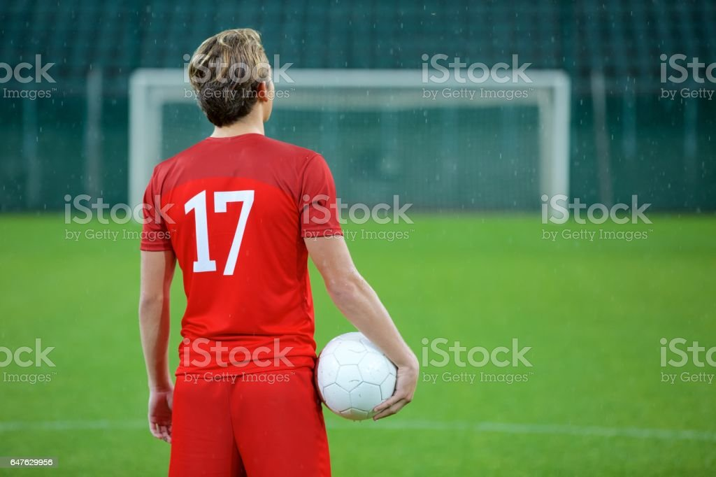 Football player standing in stadium stock photo